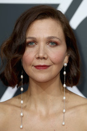 Maggie Gyllenhaal glammed up her look with a pair of pearl drop earrings that reached past her shoulders!