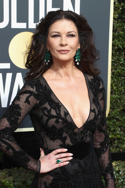 Catherine Zeta-Jones accessorized with a Lorraine Schwartz emerald ring and matching earrings for a pop of color to her black gown at the 2018 Golden Globes.