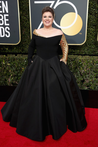 Kelly Clarkson attended the 2018 Golden Globes looking like royalty in a black and gold off-the-shoulder ball gown by Christian Siriano.