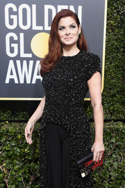 Debra Messing went for edgy styling with a metal plate-embellished clutch at the 2018 Golden Globes.