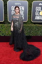 Debra Messing looked opulent in a caped, sequined, and feathered gown by Pamella Roland at the 2019 Golden Globes.