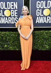 Michelle Williams hit the Golden Globes red carpet wearing an asymmetrical orange empire-waist gown by Louis Vuitton.