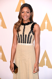 Naomie Harris accessorized with an elegant black and gold tube clutch by Edie Parker at the Academy Awards nominees luncheon.