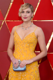 Greta Gerwig contrasted her yellow gown with a blue Roger Vivier satin purse with a bejeweled handle at the 2018 Oscars.