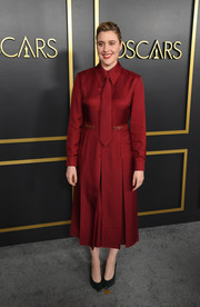 Greta Gerwig was office-chic in a long-sleeve red Gucci shirtdress with a matching necktie at the 2020 Oscar nominees luncheon.