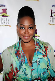 Tichina Arnold boldly accessorized with a pair of dangling earrings that reached down almost to her tummy.