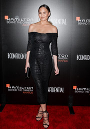 Chrissy Teigen looked phenomenal in a croc-textured black off-the-shoulder dress by Nicholas Oakwell Couture at the Hamilton Behind the Camera Awards.