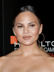 Chrissy Teigen complemented her 'do with a pair of diamond hoops.
