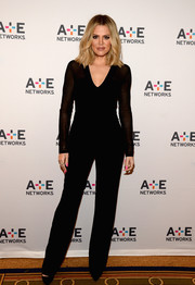 Khloe Kardashian cut a sleek figure in her black jumpsuit with sheer sleeves for a polished outfit.