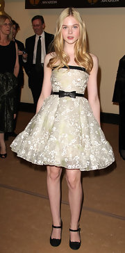 Elle Fanning looks lovely in age appropriate black maryjane heels. The adorable bow-adorned shoes complement a feminine frock with a matching bow belt.