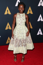 Lupita Nyong'o polished off her look with gold cross-strap sandals.