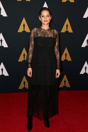 Marion Cotillard contrasted her delicate dress with edgy black patent boots, also by Dior.