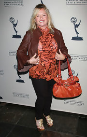 Charlene Tilton played with earth hues as she wore an orange top, wooden heeled sandals, an orange purse, and a brown leather jacket for the Emmy reception.