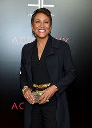 Robin Roberts attended the premiere of 'Acrimony' carrying an elegant chevron-patterned gold clutch.