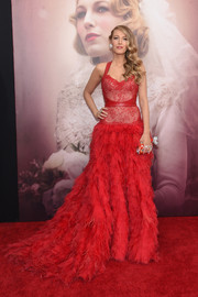 Blake Lively stunned at the 'Age of Adaline' New York premiere in a scene-stealing red Monique Lhuillier corset gown, featuring a lace bodice and a voluminous layered skirt.