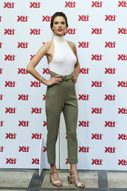 Alessandra Ambrosio teamed her sexy top with high-waisted olive-green pants.