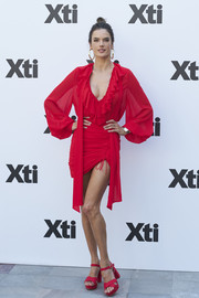 Alessandra Ambrosio showed off her endless legs in a red mini dress by Ester Abner with a low, ruffled neckline and a ruched skirt while presenting Xti's new collection.