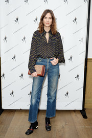 Alexa Chung contrasted her modest blouse with edgy bootcut jeans.