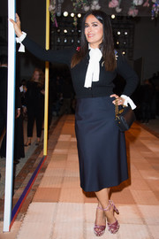 Salma Hayek looked preppy in a black cardigan layered over a white pussybow blouse at the Alexander McQueen Spring 2018 show.