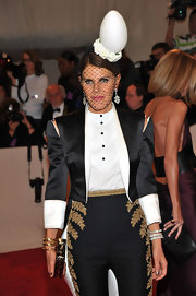 Anna dello Russo walked the red carpet in a sharp tuxedo suit and a large egg head piece.