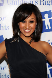 Tamera Mowry styled her hair in a straight shoulder length hairstyle while sweeping her bangs across her face.