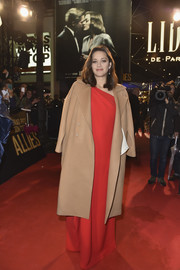 Marion Cotillard arrived for the Paris premiere of 'Allied' wearing a beige wool coat over a red one-shoulder gown.