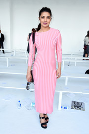 Priyanka Chopra showed off her svelte figure in a body-con bubblegum-pink sweater dress by Altuzarra when she attended the label's fashion show.