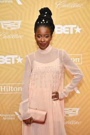 Amanda Gorman matched a pale pink satin clutch with a pleated cocktail dress for the American Black Film Festival Honors.