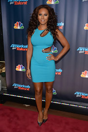 Mel B showed off her daring style with this turquoise body con dress with bronze embellished cutout detailing.