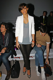 Frankie Sandford paired a white blazer over a sheer, gray top for a sleek and sophisticated look at the Aminaka Wilmont fashion show in London.
