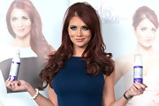 Amy Childs wore her hair in long loose curls while  promoting new self-tanning products.