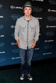 Dax Shepard paired his printed fedora hat with a grey button down shirt.