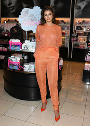 Taylor Hill looked subtly sexy in a sheer orange knit top while introducing Victoria's Secret's new Teaser Dreamer fragrance collection.