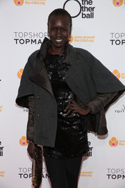 Alek Wek arrived at the Other Ball fundraiser wearing an ultra-stylish gray pea coat over a sequined dress.