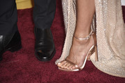 Jennifer Aniston walked the Oscars red carpet wearing a pair of rose-gold satin ankle-strap sandals by Stuart Weitzman.