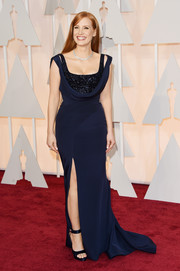 Jessica Chastain attended the Oscars wearing a vintage-glam navy Givenchy Couture gown featuring a thigh-high slit and a cowl neckline with a sparkly underlay.