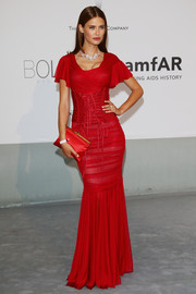 Sticking to an all-red motif, Bianca Balti accessorized with a an elegant satin clutch.
