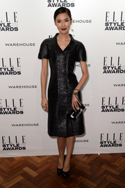 Tao Okamoto kept her look classic in a black Chanel coat dress during the Elle Style Awards.