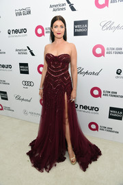 Bellamy Young put on a leggy display at Elton John's Oscar-viewing party in a deep-red Tony Ward Couture strapless gown with an up-to-the-hip slit.
