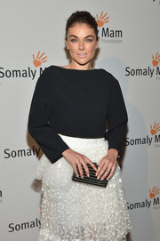 Serinda Swan paired a simple black blouse with a frilly white skirt for her Life is Love Gala look.