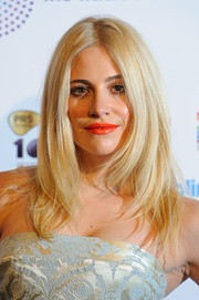 Pixie Lott brightened up her beauty look with red-orange lipstick.