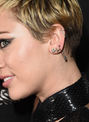 Miley Cyrus wore a total of five earrings in one ear when she attended the amfAR Inspiration Gala, including a pair of studs and a safety pin!