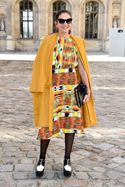 Audrey De Broglie layered a mustard wool coat over a vibrant print dress for the Christian Dior fashion show.