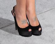 Kelly Osbourne gave herself a boost in a pair of black satin peep-toe pumps.