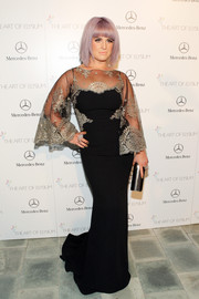 Kelly Osbourne cut a regal figure at the Art of Elysium's Heaven Gala in a black Badgley Mischka gown with a lace bodice and bell sleeves.
