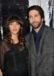 Zoe Buckman styled her brunette tresses in soft curls with blunt cut bangs.