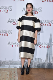 Marion Cotillard cleverly disguised her baby bump in a loose, boldly striped Dries Van Noten dress for the 'Assassin's Creed' photocall in Paris.