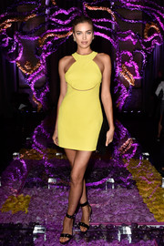 Irina Shayk was retro-sexy in a yellow halter mini dress during the Atelier Versace fashion show.