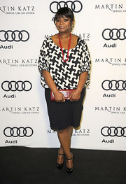 Octavia Spencer added kick to her black-and-white graphic print blouse with lipstick red accessories.