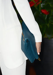 Clair Holt chose an oversized fold-over clutch in a vibrant blue to bring some color to her white pantsuit.
